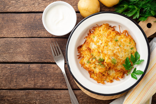 Potato pancakes or latkes or draniki in plate on dark wooden table. Top view. Copy space.