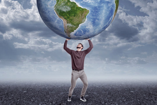 Full length front view of young man in casual clothes holding up big Earth globe on gloomy overcast day.