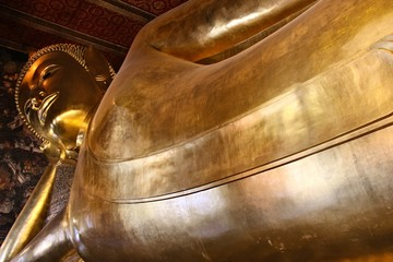 Reclining buddha statue in Wat Pho temple, Bangkok, Thailand. This is a popular tourist attraction in the city.