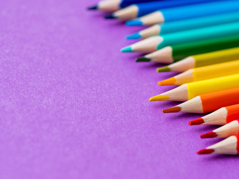 Row of colorful watercolor pencils on lilac background. School supplies on purple paper background. Kid's stationery. Back to school magenta backdrop.