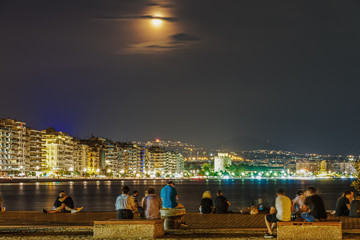August 2019 full moon over Thessaloniki, Greece waterfront. Moon rising over White Tower landmark, seen from the city port.