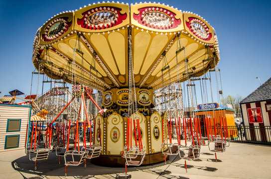 APRIL 30 2019 - BROOKLYN NEW YORK: Lynn's Trapeze, a swinging chairs carnival ride awaits riders on a spring day at Luna Park, on the Coney Island Boardwalk