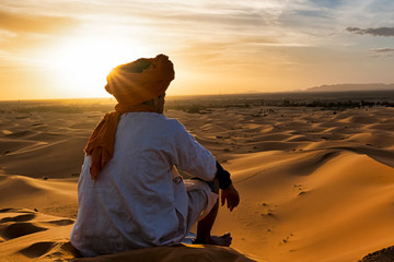 View from behind of a young native of the desert who observes the dunes in the desert of Morocco at sunset, the sun gives orange colors and is above its head, is dressed in typical clothes
