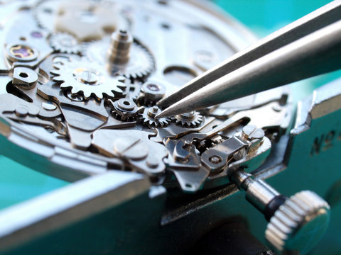 close up of watchmaker repairing old watch meachism, taking small gear with tweezers