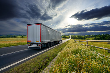 Fotobehang - Truck driving on the asphalt road in rural landscape at sunset with dramatic clouds