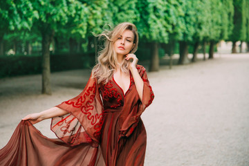 Portrait of a blond woman with flying hair in a red, wine color dress. Gentle makeup, Natural beauty with minimal retouching and without processing. Bloody Countess Bathory. Art horizontal photography