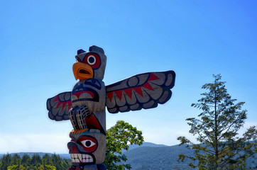 close-up of native Americans totem on a background of the sea bay surrounded by mountains and coniferous forest. Cowichan Valley, Vancouver Island, Canada Wall mural
