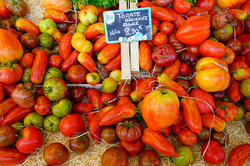 Crate of colorful organic heirloom tomatoes at the farmers market