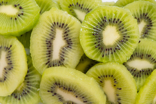 Many kiwi slices are placed in a glass crisper. Kiwifruit slices without peel.