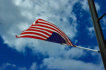 A close up of an American flag blowing on a flagpole