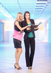 Two girls in the office with folders with papers in hand. Young women discuss office work.