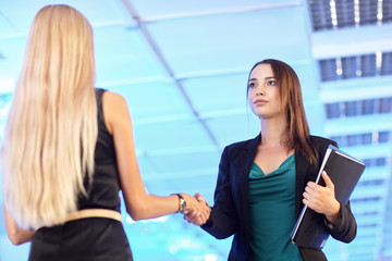 Two young women in the office with folders with papers  shake hands