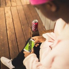 Person playing a mobile game while drinking coca-cola