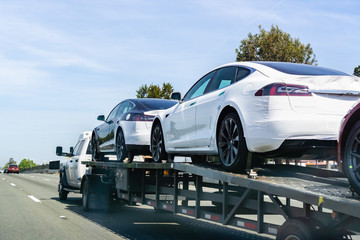 April 26, 2019 Redwood City / CA / USA - Car transporter carries Tesla Model 3 new vehicles along a highway in San Francisco bay area, back view of the trailer;