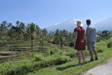 Tourist couple looking at the landscape view of rice fields in Jatiluwih rice terraces Bali Indonesia