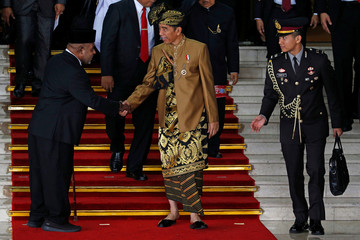 Indonesia's President Joko Widodo greets a parliament member as he departs after delivering address ahead of Independence Day at the parliament building in Jakarta