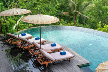 Canvas Prints Bali View of the swimming pool water and sunbeds in the tropical jungle near Ubud, Bali, Indonesia , top view