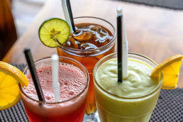 Avocado smoothie, watermelon shake and cold tea in a glass on a wooden table. Tropical drink concept . Top view, closeup