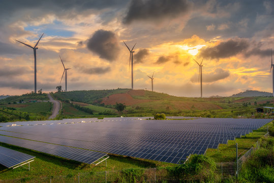 solar panels and wind turbines generating electricity in power station green energy renewable with sunset  background