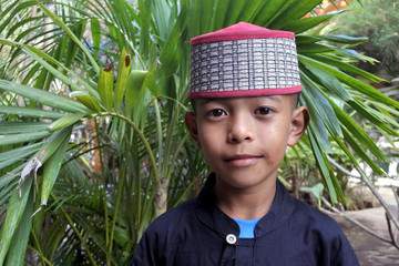 Muslim Indonesian boy dressed in traditional clouting looking at camera