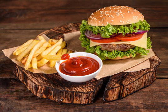 Tasty grilled homemade burgers with beef, tomato, cheese, cucumber and lettuce. Delicious grilled burgers. Craft beef burger and french fries on wooden table