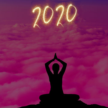 Good intentions for new year 2020: woman silhouette doing yoga