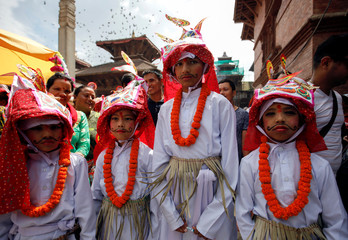Boys dressed in white depicting holy cows participate in a parade to mark Gaijatra Festival in Kathmandu