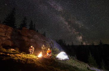 Night camping in the mountains. Happy couple travellers sitting together beside campfire and glowing tourist tent. On background big boulder, forest and night starry sky full of stars and Milky way.