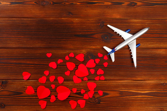 White blank model of passenger airplane on shapes of heart over wooden background .