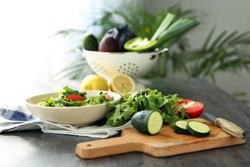Preparing of tasty salad with arugula on table