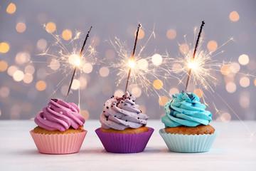 Tasty Birthday cupcakes on table against defocused lights