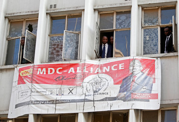 People peer through the windows of the headquarters of the  opposition Movement for Democratic Change (MDC) party after police earlier banned planned protests in Harare