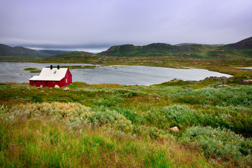 Landscape with isolated house on the plateau of Hardangervidda National Park.