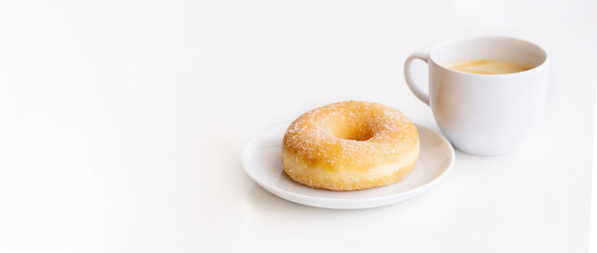 Cup of coffee with classic sugar donut on white background for banner with copy space.Good morning and breakfast concept