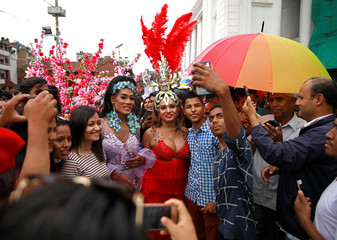 People gather to take pictures with the revellers during the LGBT pride parade to mark Gaijatra Festival, also known as the festival of cows in Kathmandu
