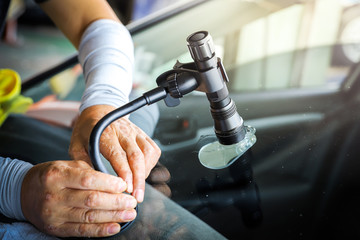 The broken car glass being repaired using professional equipment.