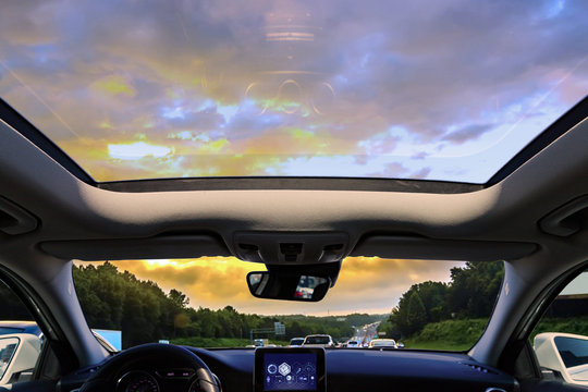 a car sunroof and sunset