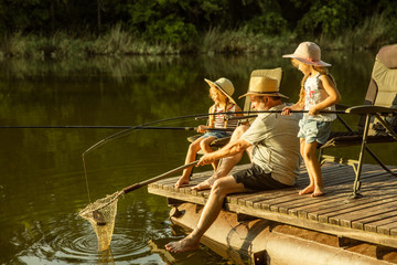 Poster Peche Cute little girls and their granddad are on fishing at the lake or river. Resting on pier near by water and forest in sunset time of summer day. Concept of family, recreation, childhood, nature.