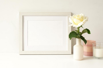 White frame mock up on white wall, rose in a vase, decorative candles . Home decor close up. Copy space