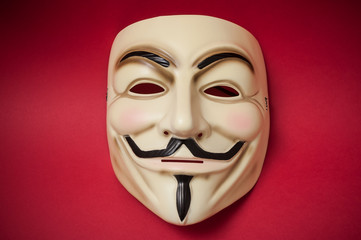 Mulhouse - France - 17 January 2019 - Vendetta mask on red paper background . This mask is a well-known symbol for the online hacktivist group Anonymous