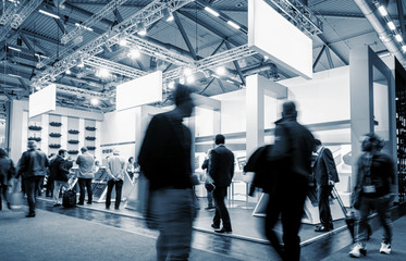 business people walking at a trade show booth at a public event exhibition hall, with banner and copy space for individual text