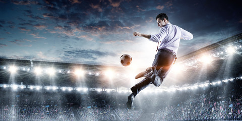 Young businessman playing footbal in action