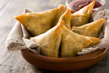 Samsa or samosas with meat and vegetables in bowl on wooden table. Traditional Indian food