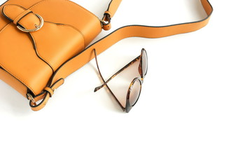 women fashion  accessories top view on white background. Flat lay with bag  and sunglasses in orange colors. Copy space