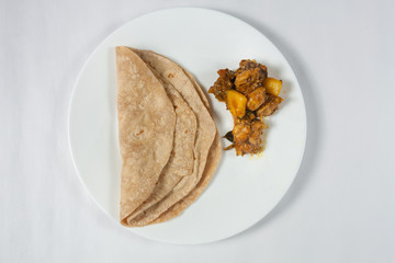 Top view of a plate of Indian Chapati and Chicken Curry