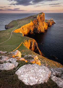 Neist Point, famous landmark with lighthouse on Isle of Skye, Scotland lit by setting sun.