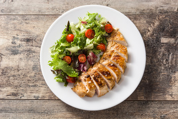 Grilled chicken breast with vegetables on a plate on wooden table. Top view.
