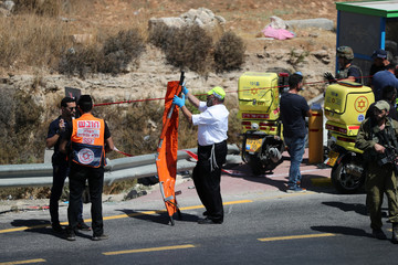 Israeli forces and members of Zaka Rescue and Recovery team work near the scene of what Israeli military said is a car-ramming attack near the settlement of Elazar in the Israeli-occupied West Bank