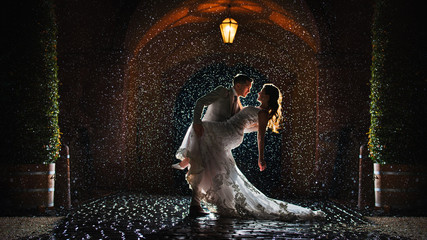 a bride and groom is dancing happily in the rain Fototapete