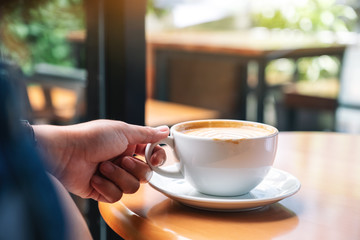 Closeup image of a hand holding a cup of hot coffee on table